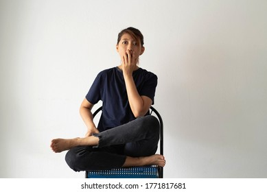 Woman sitting against on the wall,raise hand cover mouth,wide eyes.Shocked and frightened emotion,body language