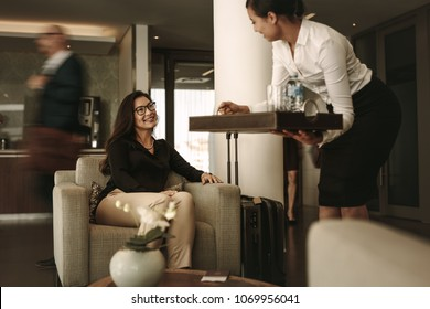 Woman sitting at airport lounge with waitress serving coffee. Business traveler at airport waiting lounge.