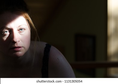 A woman sitting alone in the dark with a moody dark and light shadow on her face just enough to show she might be suffering from lack of self love, depression or some other mental illness.