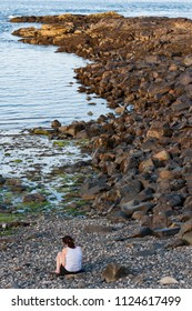 Woman sitting alone on a rock looking at turquoise clear water of Atlantic Ocean, Maine USA