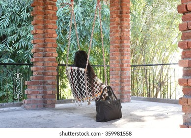 A woman sitting alone on a swing amidst of pillars made up of bricks at sunrise