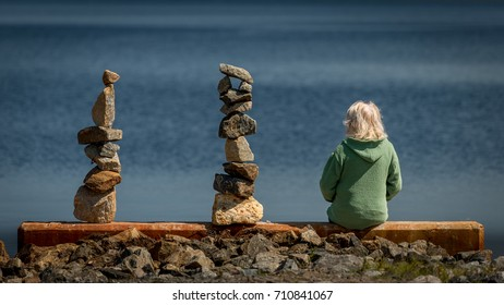 A woman sitting along side two balanced rock piles (cairns) along the shore of Tupper Lake in the Adirondacks, New York