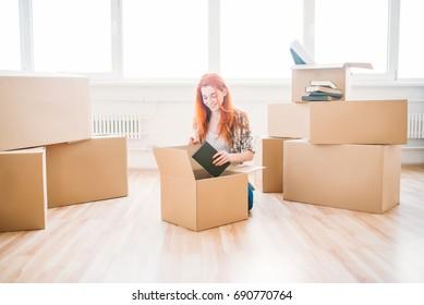 Woman sitting among cardboard boxes, housewarming