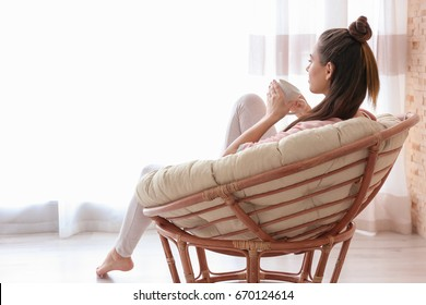 Woman sitting in armchair and drinking coffee