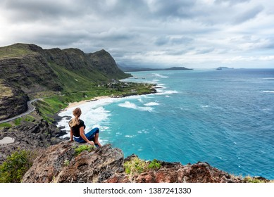 Woman sitting atop a cliff overlooking Oahu, Hawaii's south shore