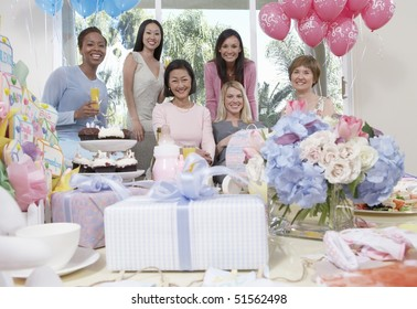 Woman sitting at baby shower behind table of gifts