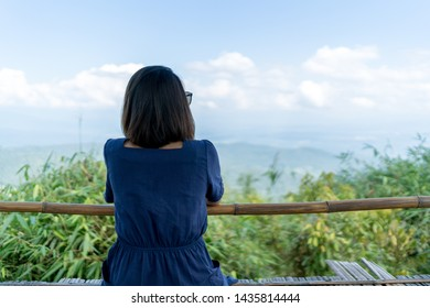 Woman sitting backwards and watching mountainous country landscape.