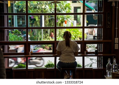 A woman sitting at the bar alone enjoy her dessert in cafe.