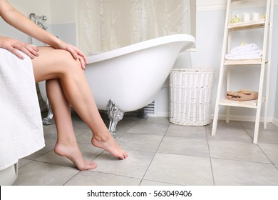 Woman sitting in bathroom, closeup of female legs on bath background
