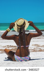 woman sitting at beach with straw hat