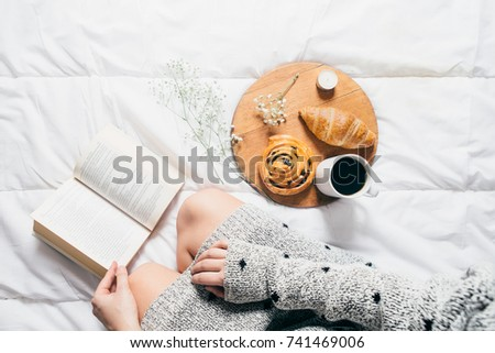 Woman sitting in bed reading a book and having breakfast. Top view