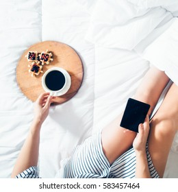 Woman sitting in bed using mobile phone and having breakfast. Top view