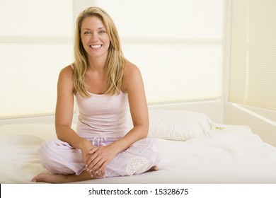 Woman sitting in bedroom smiling