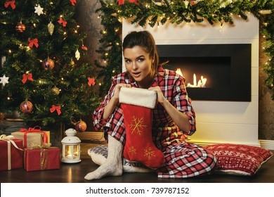 Woman sitting beside fireplace and searching gifts in Christmas stocking