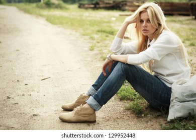 The woman sitting beside the road with a bag