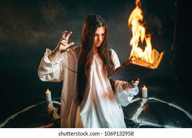 Woman sitting in burning pentagram circle, magic