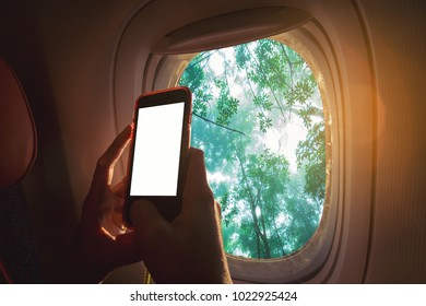 Woman sitting by aircraft window and using a digital mobile during the flight. Green forest as seen through window of an aircraft.