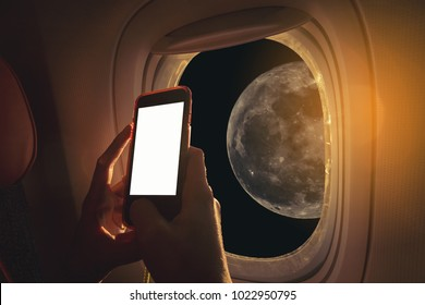Woman sitting by aircraft window and using a digital mobile during the flight. The moon as seen through window of an aircraft.