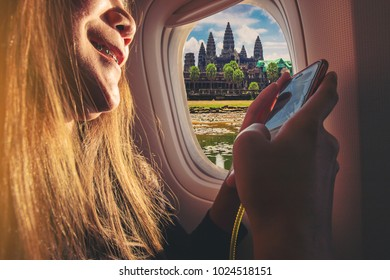 Woman sitting by aircraft window and using a digital mobile during the flight. Angkor wat in Cambodia as seen through window of an aircraft.