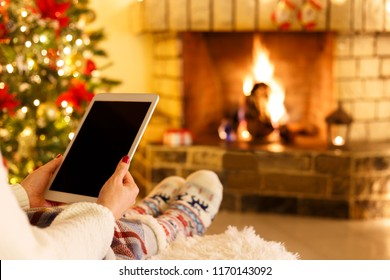 Woman sitting by fireplace and christmas tree using tablet holiday cozy concept
