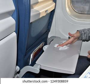 A woman sitting by a window seat is wiping down a germ laden dirty airplane tray with an antibacterial wipe illustrating the effort to stay healthy during air travel.