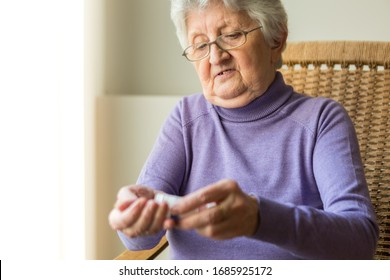 Woman sitting by the window taking the pills out of pill bottle.