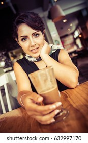 Woman sitting in cafe with coffee drink