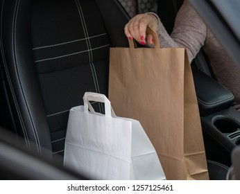 Woman sitting in car and holding two paper bags.
