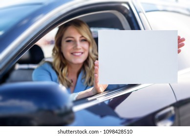 Woman sitting in the car and holding a white blank poster. Attractive blonde with a clean sheet of paper or your text. Focus on paper.