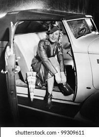 Woman sitting in a car putting on her shoes