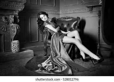 Woman sitting in chair in long claret, purple dress. Noir, vintage, retro