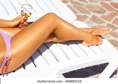Woman  sitting in chaise lounge with glass of wine