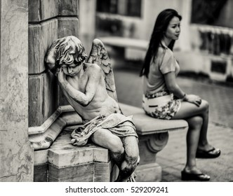 Woman sitting with the child angel statue in the La Recoleta Cemetery in Buenos Aires, Argentina