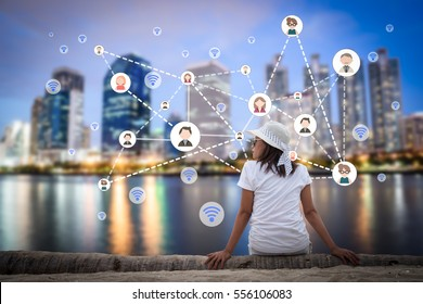 Woman sitting in the city park near the river with people and multimedia icon. Technology networking concept.