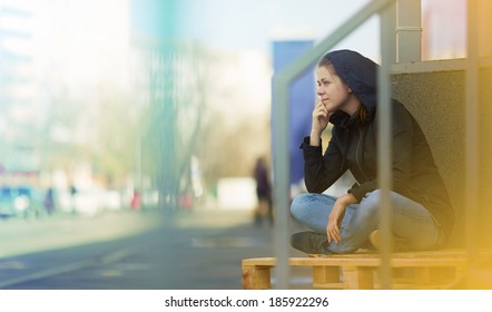 Woman sitting in city. Street photo. Outdoor.