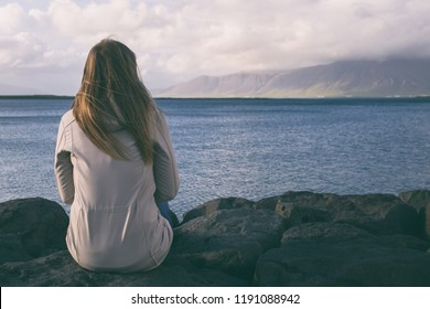 Woman sitting at the coastline in Reykjavik and looking at the sea.Image contains little noise because of high ISO set on camera and it is intentionally toned.
