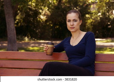 Woman sitting with coffee or tea on park bench.