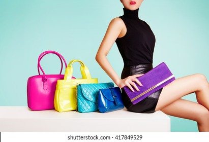 Woman sitting with colorful bags. leather products fashion image.