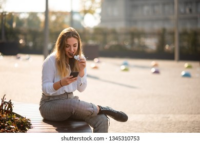 Woman sitting with crossed leg eating energy bar