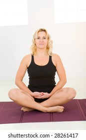 Woman sitting cross-legged on mat. She's smiling and looking at camera. Front view.
