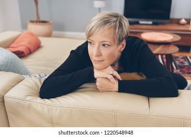 Woman sitting daydreaming at home leaning over the back of the sofa staring into the distance with a serious faraway expression