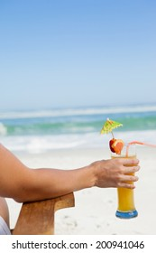 Woman sitting in deck chair with a cocktail at the beach on a sunny day