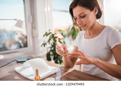 Woman sitting at the desk by the window and paining nails at home