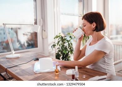 Woman sitting at the desk by the window drinking coffee while drying nails with UV led lamp