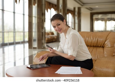 a woman sitting at a desk with a phone and a tablet