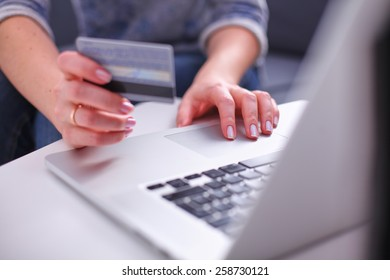 Woman sitting at the desk, shopping with laptop and credit card