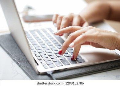 Woman sitting at desk and working at computer close up in hands.