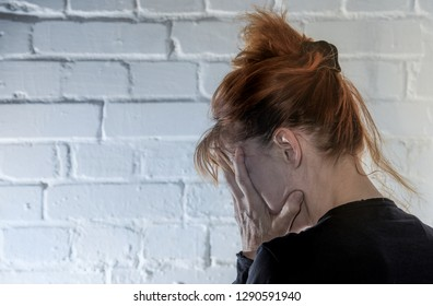a woman is sitting desperately in front of a wall