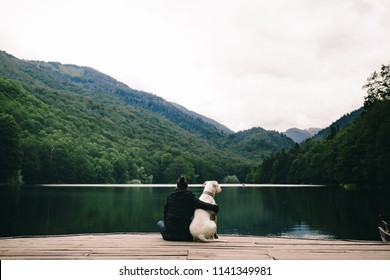 Woman sitting with a dog on dock at the lake