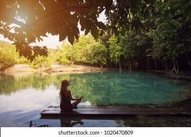 Woman sitting and doing yoga near Emerald Pool (Sa Morakot), Krabi Thailand, Crystal clear blue and green water at the lake,  Natural forest in Thailand